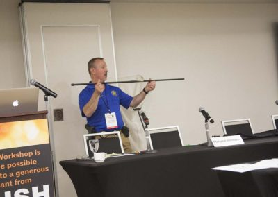 "Ken Holmes demonstrates blow dart equipment during ""Caregiving: Safe Capture"""