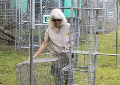 Kari Bagnall demonstrates a transport cage during the tour of Jungle Friends Primate Sanctuary